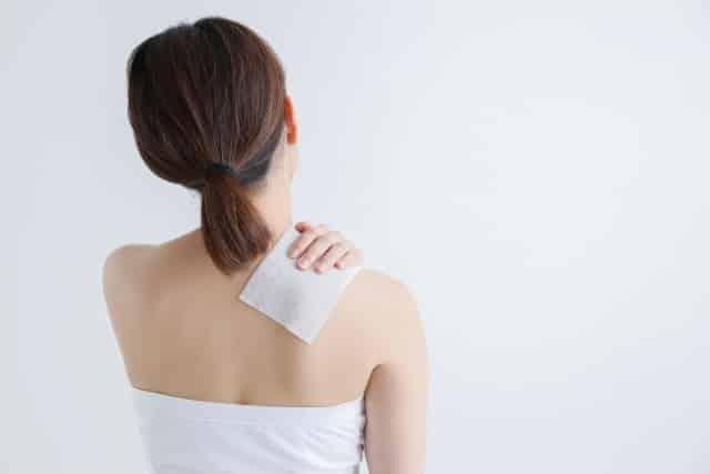 肩にシップを貼る女性